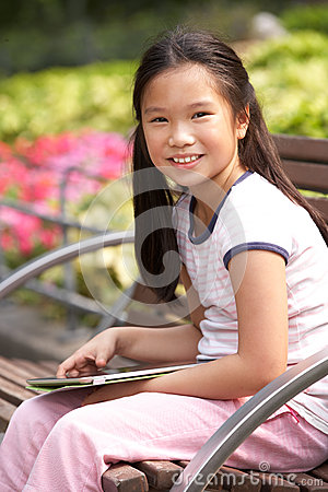Portrait Of Chinese Girl Sitting On Park Bench