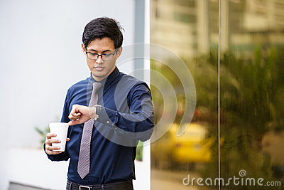 Portrait of chinese office worker checking time watch