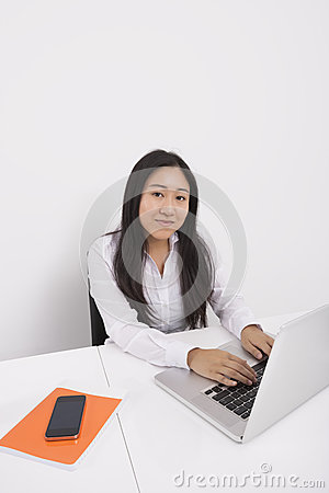 Portrait of confident businesswoman working on laptop in office
