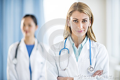 Portrait Of Confident Doctor Standing In Clinic