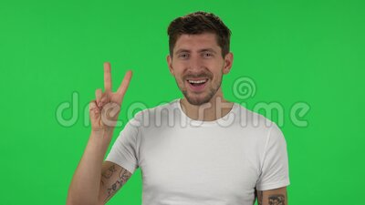 Portrait of confident guy is showing two fingers victory gesture. Green screen. Portrait of confident guy is showing two fingers victory gesture. Bearded brown stock video footage