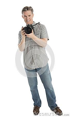 Portrait Of Confident Photographer With Camera And Umbrella Ligh