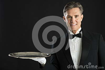 Portrait Of Confident Waiter Carrying Serving Tray