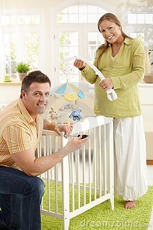 Portrait of couple fixing baby bed