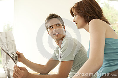 Portrait of Couple Sharing Newspaper at Home