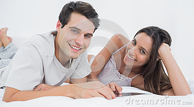 Portrait of a couple using a tablet lying in bed