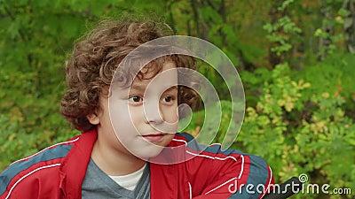 Portrait curly brunette boy no parque de verão Feche a cara do adolescente de bicicleta no parque verde Garoto bonito procurando filme