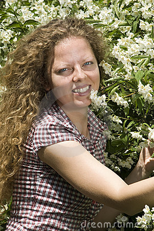 Portrait of a curly girl near jasmine flowers
