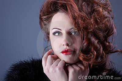 Portrait of a curly red-haired girl with red lips