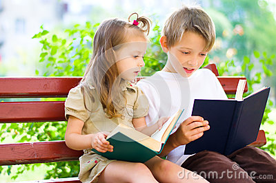Portrait of cute kids reading book