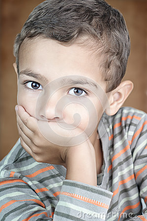 Portrait of cute litle boy covering his mouth