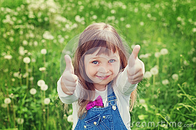 Portrait of cute little girl with thumbs up shows a class on the flower meadow, happy childhood concept, child having fun Stock Photo