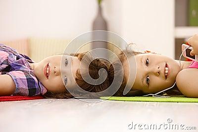 Portrait of cute schoolgirls listening to music