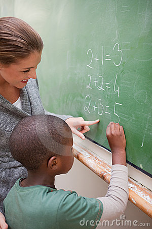 Portrait of a cute teacher and a pupil making an addition