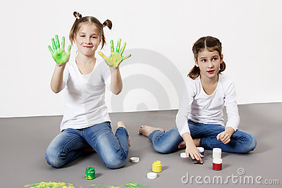 Portrait of cute twin girls with finger paintings