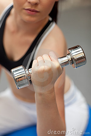 Portrait of a cute woman working out with dumbbell