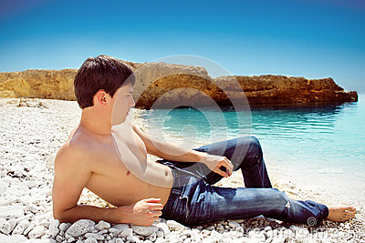 Portrait of cute young man on the beach, blue sky