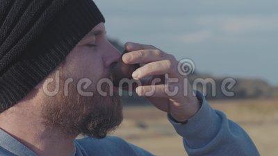 Portrait d'un hipster avec une barbe buvant du thé dans un bol à l'extérieur cérémonie du thé chinois Vidéo 4k 59 94 fps clips vidéos
