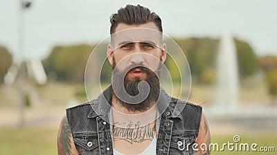 Portrait d'un homme brutal et barbu avec des tatouages sur ses épaules banque de vidéos
