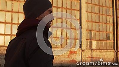 Portrait d'un homme marchant au-dessus de bâtiments industriels et au coucher du soleil clips vidéos