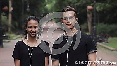 Portrait d'un jeune Caucasien et d'une jeune femme au casque qui a l'air heureux debout dans le concept de Park People banque de vidéos