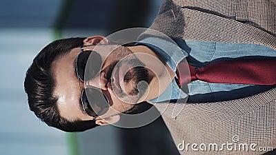Portrait d'un jeune homme d'affaires prospère portant un costume et des lunettes de soleil debout dans la rue Vidéo verticale Gro clips vidéos