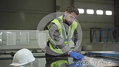 Portrait d'un jeune homme caucasien mesurant des tôles en acier Professionnel de confiance dans la veste et les gants de travail banque de vidéos