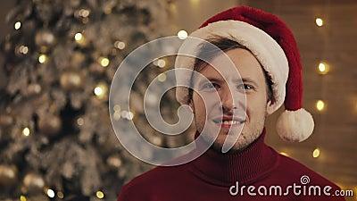 Portrait d'un jeune homme souriant et attrayant portant un chapeau de Santas et un chandail d'hiver rouge assis à l'arbre de Noël banque de vidéos