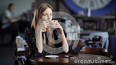 Portrait d'une belle femme dans un café ou un restaurant Une fille boit du thé ou le café et les rêves au sujet de quelque chose banque de vidéos