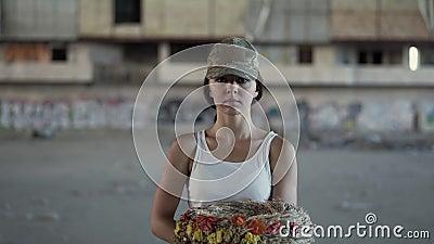 Portrait d'une belle fille dans un chapeau de camouflage et un T-shirt blanc tenant une guirlande regardant la caméra Femme de gu clips vidéos