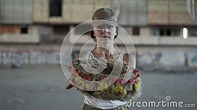 Portrait d'une belle fille dans un chapeau de camouflage et un T-shirt blanc tenant une guirlande regardant la caméra Femme de gu banque de vidéos