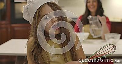 Portrait d'une fille caucasienne au fouet multicolore qui fait des visages Sa jeune mère souriante qui verse de l'eau dans la far banque de vidéos
