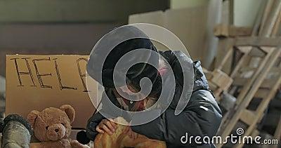 Portrait d'une fille sans abri du Caucase avec le visage sale se brisant et mangeant de façon avide le pain Enfant affamé banque de vidéos