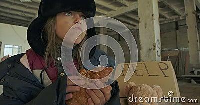 Portrait d'une sans-abri caucasienne au visage sale et aux yeux gris mangeant le pain Enfant affamé en chapeau avec banque de vidéos