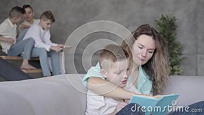 Portrait de joli jeune livre de lecture de mère à son fils tandis que le reste de ses enfants de l'adolescence jouant les uns ave clips vidéos