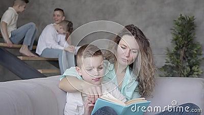 Portrait de joli jeune livre de lecture de m?re ? son fils tandis que le reste de ses enfants de l'adolescence jouant les uns ave clips vidéos