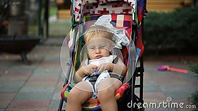 Portrait de l'adorable petit garçon blond caucasien mignon et mignon, assis à la poussette multicolore brillante et rocailleux pa banque de vidéos