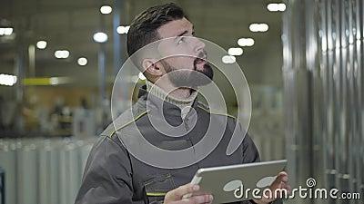 Portrait de l'homme caucasien à barbe concentré debout sur le site de production et utilisant une tablette Vérification moderne d clips vidéos