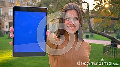 Portrait de la jeune fille caucasienne à l'aide du comprimé et montrant son affichage à la caméra sur le fond vert de parc banque de vidéos