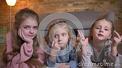 Portrait de trois petites filles caucasiennes se trouvant sur le plancher et observant dans la caméra calmement en atmosphère à l banque de vidéos