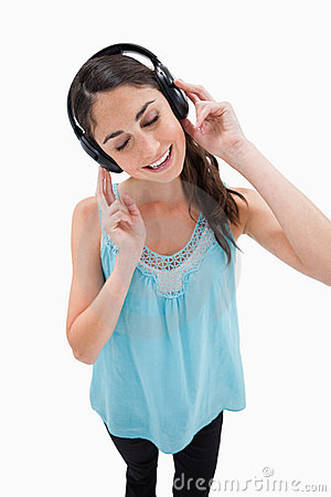 Portrait of a delighted woman listening to music