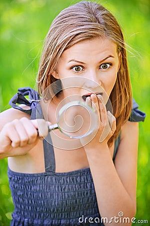Portrait der jungen Frau mit Lupe