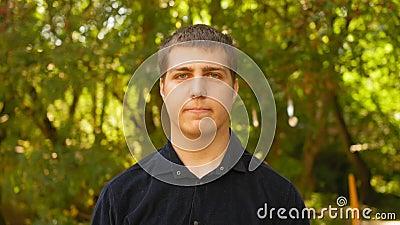 Portrait des Menschen mit einer ernstlich konzentrierten Gesichtshaut in die Kamera im Freien Nahaufnahme stock footage