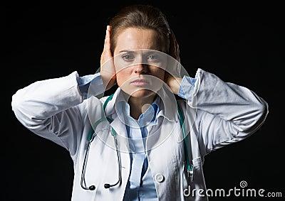 Portrait of doctor woman showing hear no evil gesture