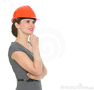 Portrait of dreaming architect woman in helmet