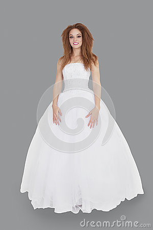 Portrait of elegant young brunette in wedding dress standing over gray background