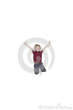 Portrait of elementary boy jumping in air with arms raised over white background