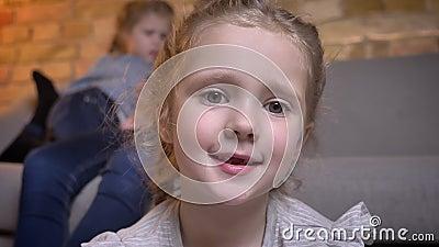 Portrait en gros plan de la petite jolie fille caucasienne avec des tresses observant timidement dans la caméra en atmosphère à l banque de vidéos