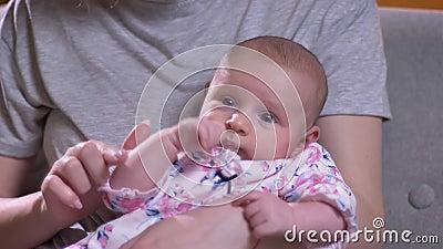 Portrait en gros plan du bébé nouveau-né mignon se trouvant sur sa mère et observant de différents côtés dans le salon banque de vidéos