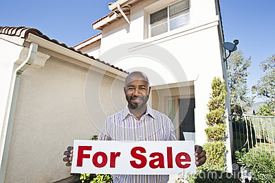Portrait Of An Estate Agent Holding ~For Sale~ Sign